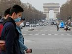 A group of tourists wearing protective masks cross the Champs Elysees avenue in Paris, Tuesday, March 17, 2020. France is imposing nationwide restrictions on how far from their homes people can go and for what purpose as part of the country's strategy to stop the spread of the new coronavirus. For most people, the new coronavirus causes only mild or moderate symptoms, such as fever and cough. For some, especially older adults and people with existing health problems, it can cause more severe illness, including pneumonia. (AP Photo/Michel Euler)