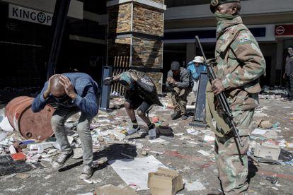 Militar vigia homens detidos por saque em um centro comercial de Soweto no dia 13.