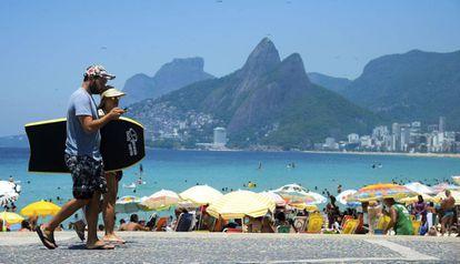 Casal caminha em praia do Rio de Janeiro.