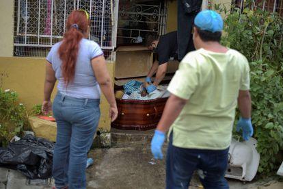 Uma mulher observa um caixão com o cadáver da sua mãe, morta pela Covid-19, na terça-feira em Guayaquil.