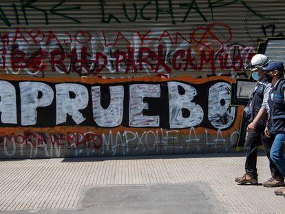 Homens passam diante de um grafite em Santiago do Chile que convoca a população a votar em favor da reforma constitucional no próximo domingo.