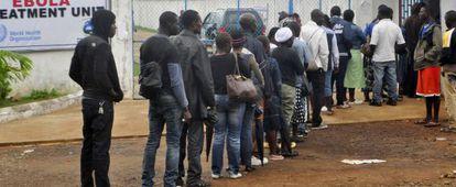 Trabalhadores da saúde da Libéria fazem fila para entrar em uma clínica de tratamento do ebola.