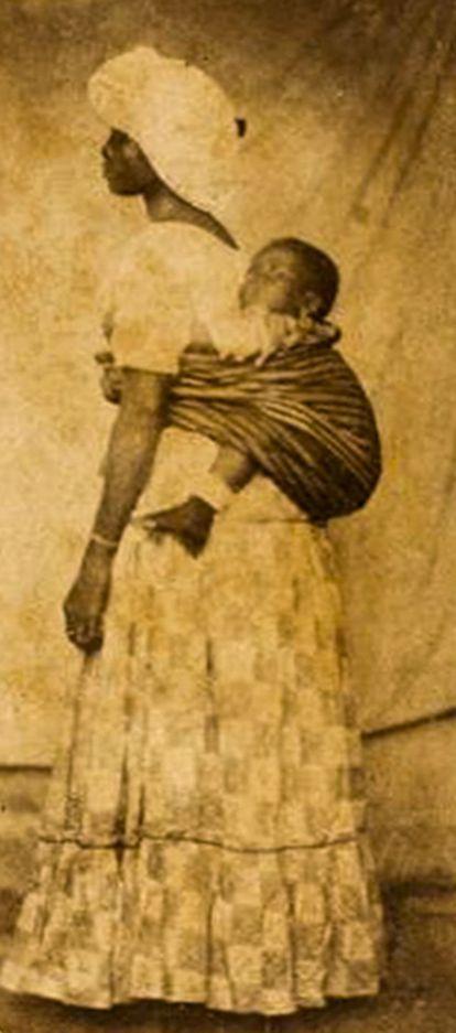 Mulher negra posando em estúdio com traje comum aos escravos brasileiros do séc. XIX: pano-da-costa utilizado para carregar criança, turbante, saia comprida.
