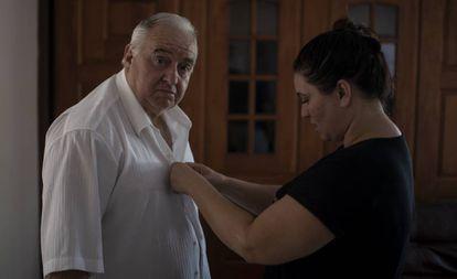Carminha arruma a camisa do pai durante a entrevista.