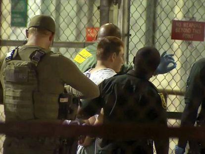 Polícias conduzem Nikolas Cruz, na quinta-feira, a um centro de detenção na Flórida.