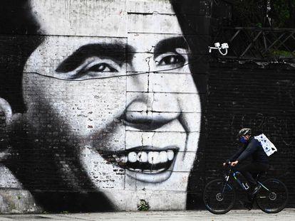 Homem com máscara passa de bicicleta em frente a mural com imagem de Carlos Gardel, em Buenos Aires, em 4 de maio de 2020.