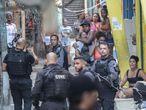 AME5642. RÍO DE JANEIRO (BRASIL), 06/05/2021.- Habitantes de una favela observan a miembros de la Policía que realizan un operativo policíal contra una banda de narcotraficantes hoy, en Río de Janeiro (Brasil). Una violenta operación policial realizada este jueves contra un grupo de delincuentes en una favela de Río de Janeiro dejó al menos 25 muertos en medio de un intenso tiroteo y en momentos en que este tipo de acciones están restringida por la justicia en la ciudad más emblemática de Brasil. Los datos oficiales señalan que un policía perdió la vida minutos después de recibir un impacto en la cabeza y que 24 sospechosos fallecieron durante el operativo en la favela de Jacarezinho. EFE/ André Coelho