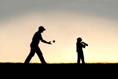 Pai joga beisebol com o filho.