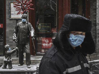 Estátuas cobertas com máscaras em uma rua de Pequim com os estabelecimentos fechados.