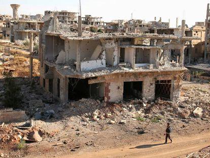 Um rebelde caminha em frente a construções destruídas na parte rebelde de Deraa.