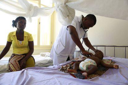 Um médico atende um bebê internado por malária em um hospital de Moçambique.