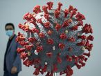 This photo taken on November 11, 2020 shows a man walking past a model of the COVID-19 coronavirus at the second World Health Expo in Wuhan, in China's central Hubei province, where the coronavirus was first detected in December 2019. (Photo by STR / AFP) / China OUT