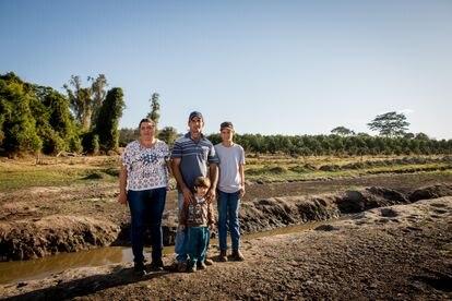 A família Reinolde dentro do açude seco, com o que restou de água no local ao fundo.