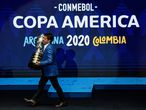 """(FILES) In this file photo taken on December 03, 2019 Brazilian former footballer Juninho Paulista presents the Copa America trophy on the stage during the draw of the Copa America 2020 football tournament at the Convention Centre in Cartagena, Colombia. - Argentina's hosting of the Copa America football tournament has been suspended """"in view of the current circumstances,"""" CONMEBOL said on May 30, 2021, as the country struggles with a surge in coronavirus cases. (Photo by Juan BARRETO / AFP)"""