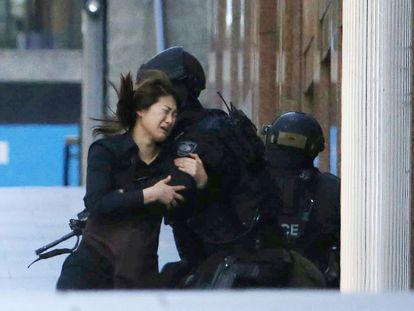 Garçonete abraça policial depois de conseguir sair do café onde homem reteve pelo menos uma dezena de pessoas reféns por 16 horas. Na segunda-feira (15) a polícia invadiu o local e colocou fim ao cerco.