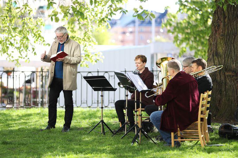 Músicos durante missa do Dia da Ascensão de Cristo nos jardins de uma igreja de Estocolmo.