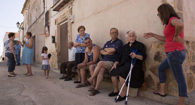 Tertulia, uma das ruas de Olmeda de la Cuesta, onde moram apenas 15 residentes fixos durante o ano. Com muletas, Flora Vergara, de 88 anos, uma das veteranas.