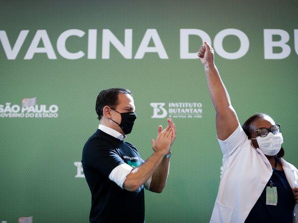 AME9923. SAO PAULO (BRASIL), 17/01/2021.- Mônica Calazans (d), enfermera del Hospital las Clínicas de la capital paulista, levanta su brazo en señal de júbilo luego de recibir la vacuna contra la covid-19 y mientras es aplaudida por el gobernador de Sao Paulo, Joao Doria (i), hoy, en Sao Paulo (Brasil). Brasil, uno de los países del mundo más afectados por la pandemia del coronavirus, aplicó este domingo en Sao Paulo la primera dosis de la vacuna contra la covid-19 a la enfermera de 54 años, en momentos en los que el gigante latinoamericano enfrenta una segunda ola de la enfermedad. La primera dosis de la vacuna desarrollada por el laboratorio chino Sinovac y el Instituto brasileño Butantan fue aplicada tan solo minutos después de la aprobación de su uso de emergencia por parte de la Agencia Nacional de Vigilancia Sanitaria (Anvisa). EFE/ Fernando Bizerra Jr