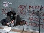 Una manifestante posa para una fotografía en el interior de un cajero Bitcoin destruido por varios manifestantes este miércoles 15 de septiembre del 2021.