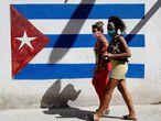 -FOTODELDÍA- HAB101. HABANA (CUBA), 02/04/2020.- Dos mujeres caminan frente a un graffiti de la bandera cubana, este jueves en La Habana (Cuba). El gobierno confirmó 21 nuevos casos positivos a la Covid-19 y llega a un total de 233 infectados. EFE/Yander Zamora