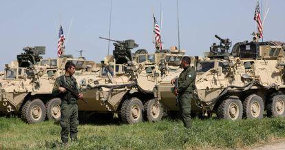 Milicianos curdos junto a veículos militares dos EUA na localidade síria de Darbasiya, perto da fronteira com a Turquia, em 2017.