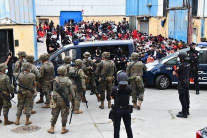A Polícia Nacional e o Exército custodiam os imigrantes nos galpões de El Tarajal (Ceuta).
