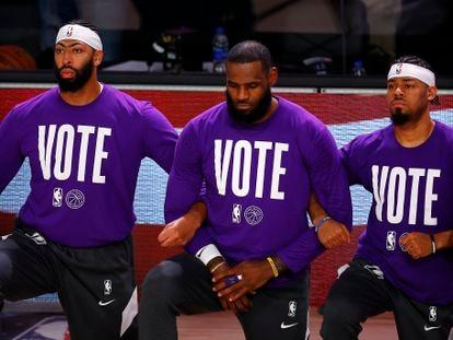 """Anthony Davis, LeBron James e Quinn Cook, dos Lakers, com o lema """"Vote"""" em suas camisetas."""