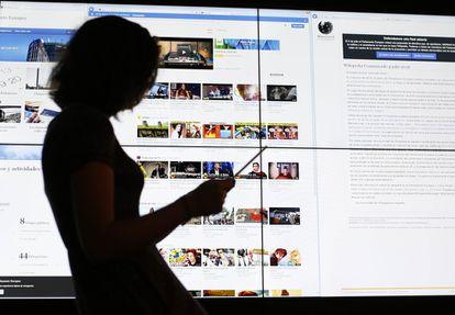 Usuária consulta um tablet em frente a uma tela com a página do Youtube.