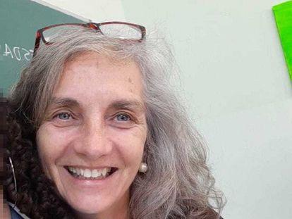 A professora de inglês Virginia Ferreira, em fotografia dentro de sala de aula com uma aluna.