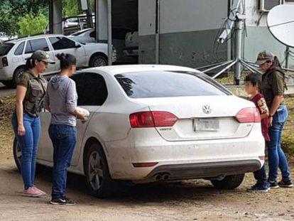 A mulher argentina sequestrada durante 32 anos (com blusão de cor cinza) entra em um carro de polícia com seu filho de 9 anos.