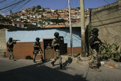 Membros da Polícia Nacional Bolivariana patrulham um bairro de Caracas, Venezuela.