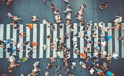 Vista vertical de uma faixa de pedestres lotada de gente.