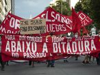 """Demonstrators hold a banner with a message that reads in Portuguese: """"Down with the Dictatorship,"""" during a protest against the Brazilian President Jair Bolsonaro coinciding with the anniversary of the 1964 military coup that established a decades-long dictatorship, in Rio de Janeiro, Brazil, Wednesday, March 31, 2021. The leaders of all three branches of Brazil's armed forces have jointly resigned following Bolsonaro's replacement of the defense minister, that is causing widespread apprehension of a military shakeup to serve the president's political interests. (AP Photo/Silvia Izquierdo)"""