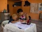 Isaac da Silva (cabelo claro), de 7 anos, e Rafael Moura (cabelo escuro), de 8 anos, retomam as atividades escolares durante a crise do coronavírus.