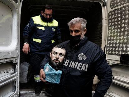 'Carabinieri' carrega o busto do falecido criminoso Emanuele Sibillo, exposto em sua capela no centro de Nápoles.