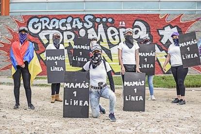 Algumas das mães da linha de frente na frente de um mural em sua homenagem.