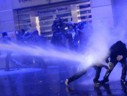 A polícia lança jatos de água contra manifestantes.
