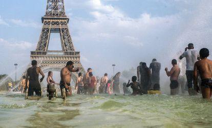 Pessoas se refrescam nas fontes dos jardins do Trocadero, em Paris.