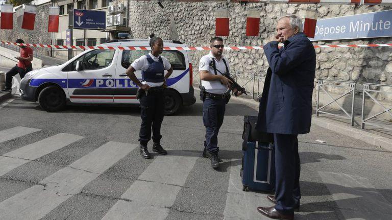 Um viajante e uns policiais franceses, em frente à estação de Marselha isolada, neste domingo.