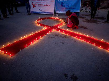 Mulheres e crianças do orfanato de recuperação para pacientes de Aids Maiti Nepal, acendem velas formando um laço vermelho, em Katmandu.