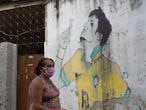 A woman, wearing a protective face mask against the spread of the new coronavirus, walks past a mural depicting Brazil's soccer star Neymar, at the Para-Pedro favela in Rio de Janeiro, Brazil, Friday, May 8, 2020. (AP Photo/Silvia Izquierdo)