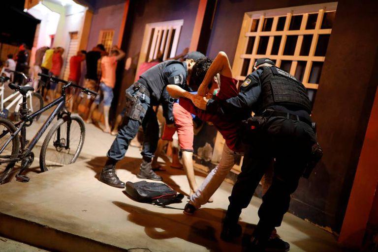 Policias revistam homem venezuelano durante operação em Boa Vista, capital de Roraima.