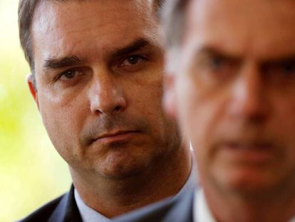 Bolsonaro, com o filho Flávio ao fundo.