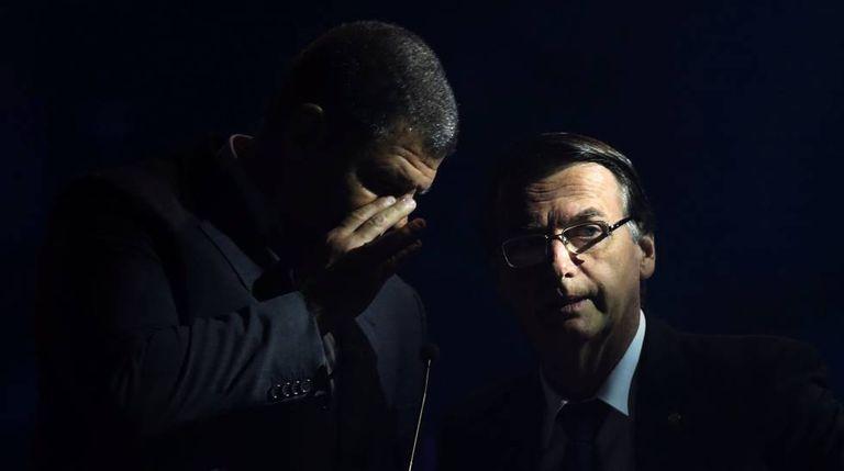 Bolsonaro conversa com assessor durante debate.