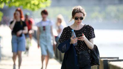 Mulher consulta telefone celular enquanto passeia em Moscou.