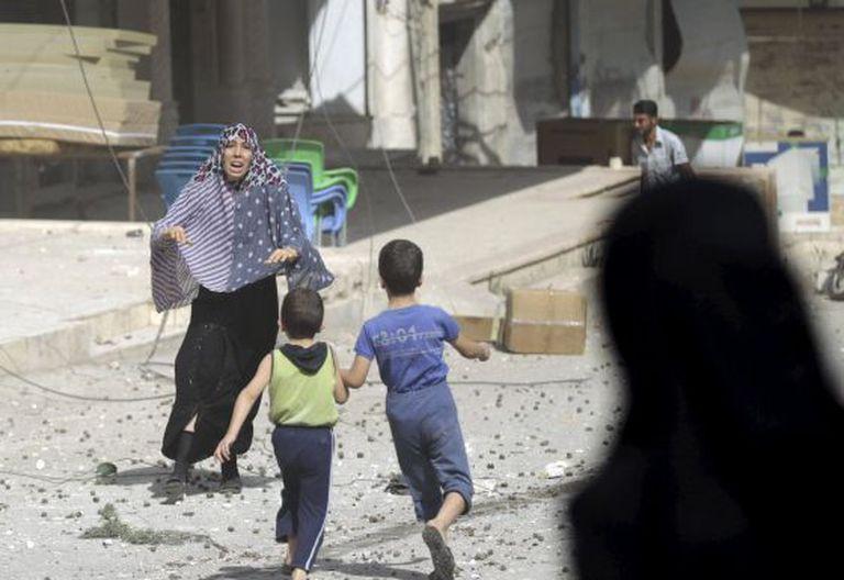 Mulher corre para pegar seus filhos após um bombardeio em Idlib, na Síria.