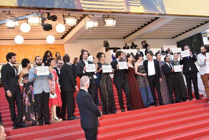 Equipe do filme exibe cartazes contra o processo de impeachment no Brasil.