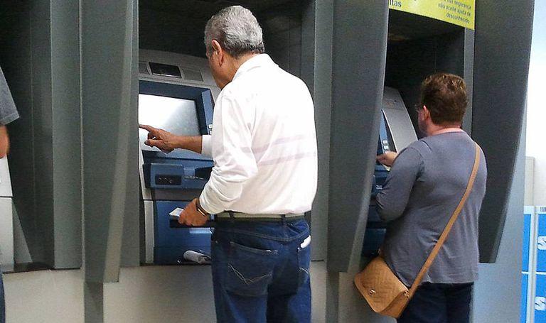 Idosos utilizam serviços bancários.