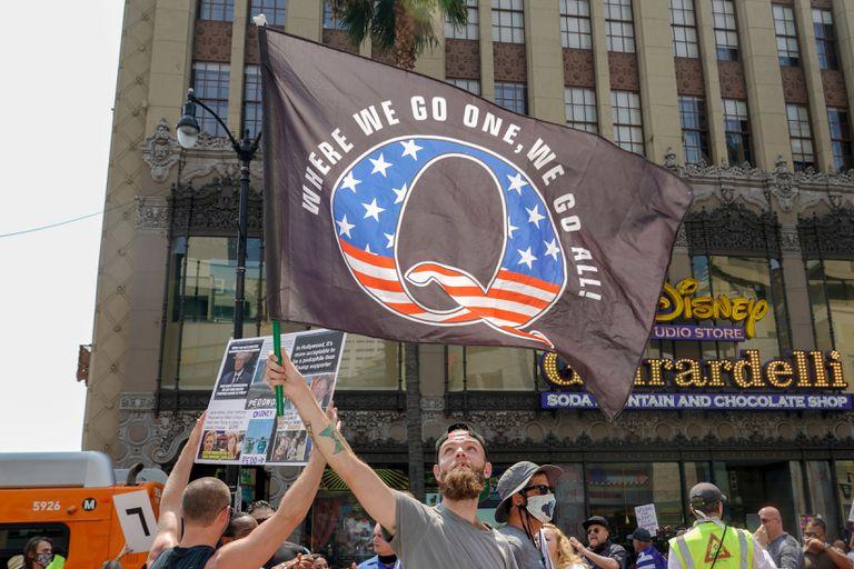 Manifestantes exibem bandeira da teoria da conspiração QAnon, em um protesto em 22 de agosto em Los Angeles.