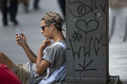 Jovem consulta celular em São Paulo.